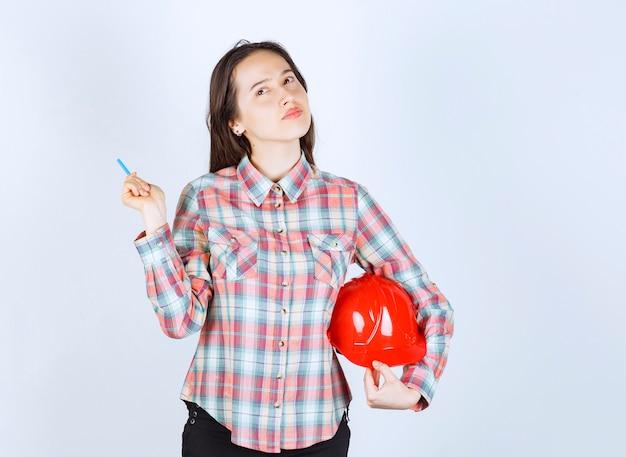 Jonge mooie architectenvrouw die veiligheidshelm met pen houdt.