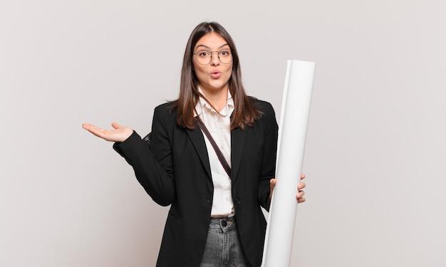 Jonge mooie architectenvrouw die verrast en geschokt kijkt, met open mond terwijl ze een object vasthoudt met een open hand aan de zijkant