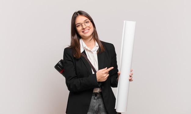 Jonge mooie architectenvrouw die vrolijk lacht, zich gelukkig voelt en naar de zijkant en naar boven wijst, een object in de kopieerruimte laat zien