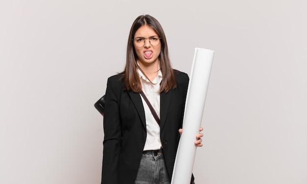 Jonge mooie architectenvrouw die walgt en geïrriteerd voelt, tong uitsteekt, een hekel heeft aan iets smerigs en vies