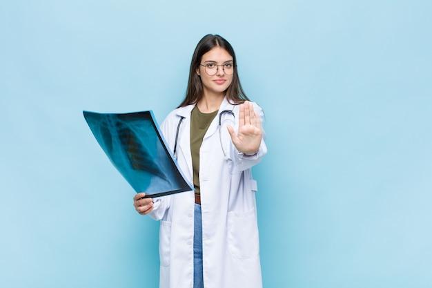 Jonge mooie arts die ernstig, streng, ontevreden en boos kijkt die open palm toont die stopgebaar maakt
