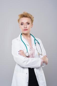 Jonge mooie arts die stethoscoop over haar hals draagt