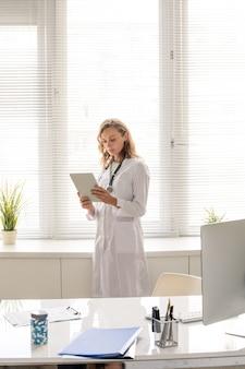 Jonge mooie arts met lang blond haar die tussen bureau met computermonitor en raam staat terwijl hij online patiënten raadpleegt