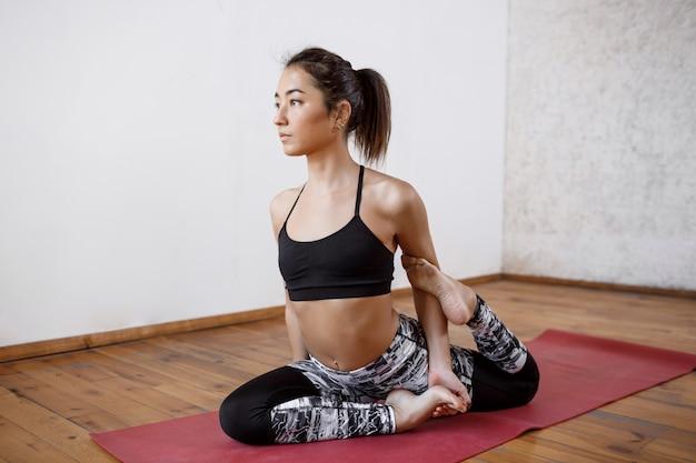 Jonge mooie atletische vrouw die binnenyoga op rode mat uitoefenen