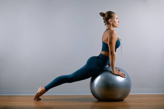 Jonge, mooie, atletische vrouw die oefeningen op fitball in de gymnastiek doet. sportieve slavische vrouw in een blauw, groen pak.