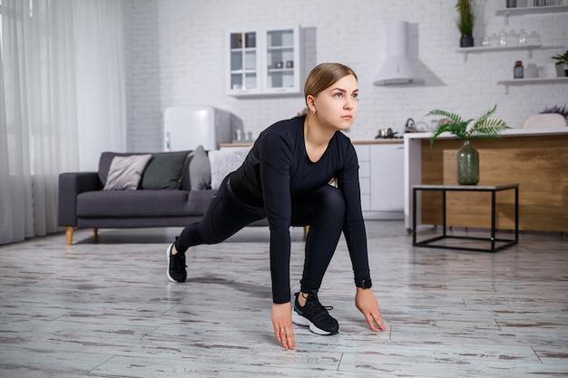 Jonge mooie atletische vrouw in zwarte legging en top warming-up oefeningen thuis doen. gezonde levensstijl. meisje in fitnesskleren. de vrouw gaat thuis sporten.