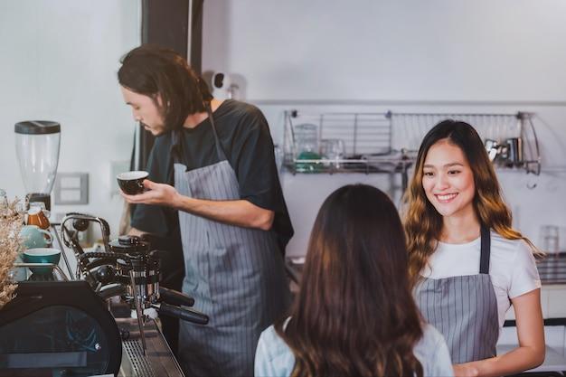 Jonge mooie aziatische de slijtageschort die van vrouwenbarista hete koffiekop houden die aan klant wordt gediend bij barteller in koffiewinkel met glimlachgezicht.