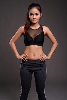 Jonge mooie aziatische fitness vrouw met slanke taille