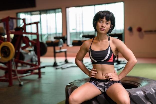 Jonge mooie aziatische fitness vrouw zit op sportschool