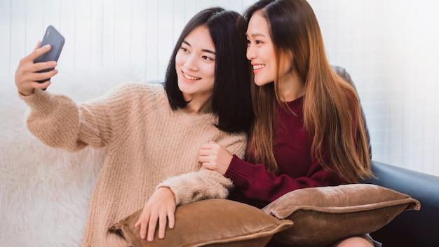 Jonge mooie aziatische lesbische paarminnaar die smartphone selfie samen in woonkamer thuis met het glimlachen gezicht gebruiken. concept van lgbt-seksualiteit met gelukkige levensstijl samen.