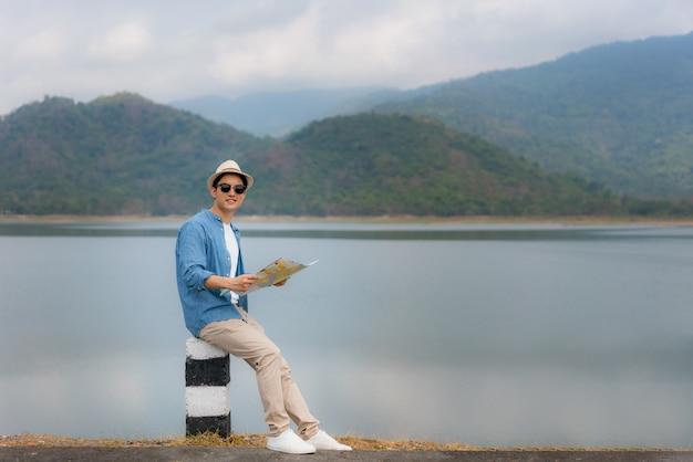 Jonge mooie aziatische man reiziger met kaart in handen en dragen zonnebril kijken en blij te zien landschapsmening zit op een meer met prachtig uitzicht op de bergen in thailand. solo man reizen
