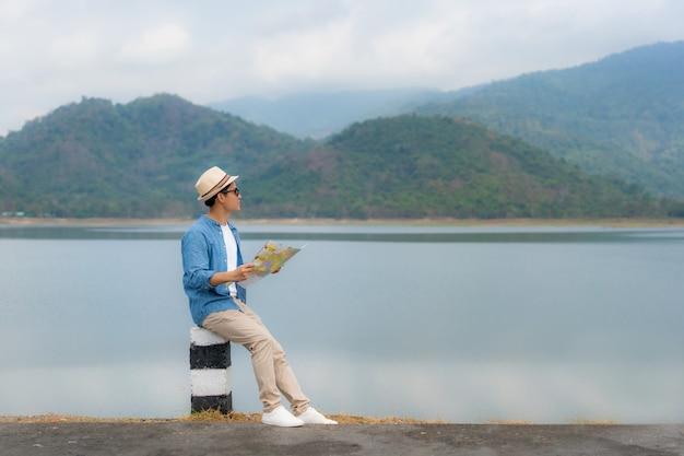 Jonge mooie aziatische man reiziger met kaart in handen en dragen zonnebril kijken en blij te zien landschapsmening zit op een meer met prachtig uitzicht op de bergen in thailand.