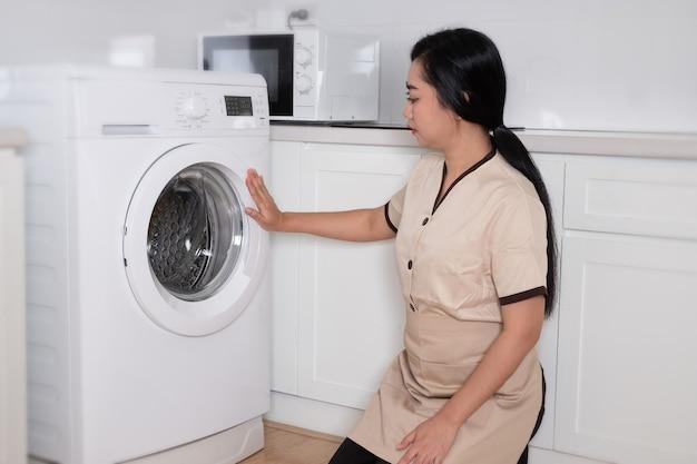 Jonge mooie aziatische meid die de kleding van de wasmachine in de hotelkamer laadt