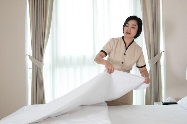 Jonge mooie aziatische meid die deken op het bed in hotelkamer schikt