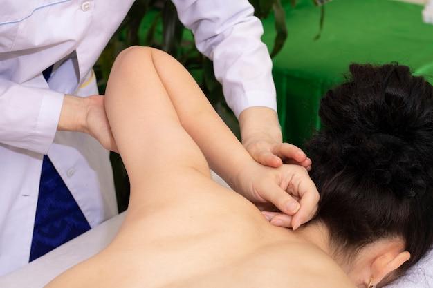 Jonge mooie aziatische meisje arm massage ontvangen