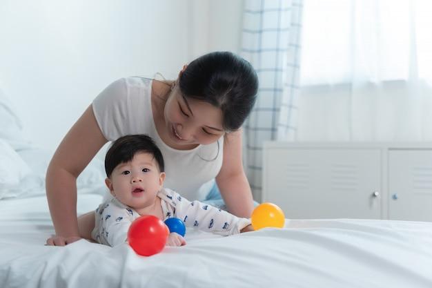 Jonge mooie aziatische moeder met aziatische baby op bed