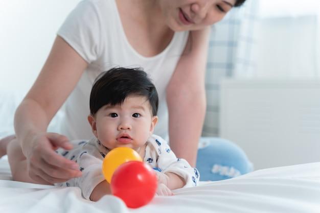 Jonge mooie aziatische moeder met haar kleine schattige baby op bed.