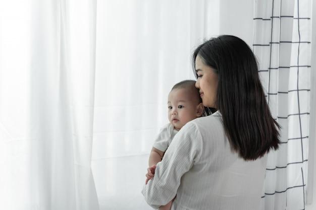 Jonge mooie aziatische moeder met haar kleine schattige pasgeboren baby thuis.
