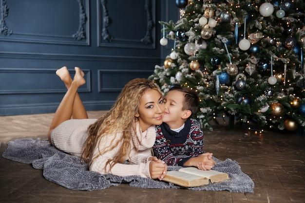 Jonge mooie aziatische moeder met haar zoontje zit in de buurt van een versierde kerstboom en het lezen van een boek.