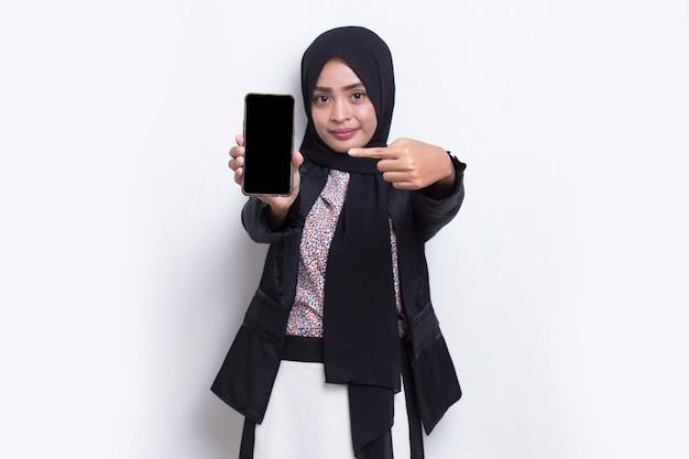 Jonge mooie aziatische moslimvrouw demonstreren mobiele telefoon geïsoleerd op een witte achtergrond