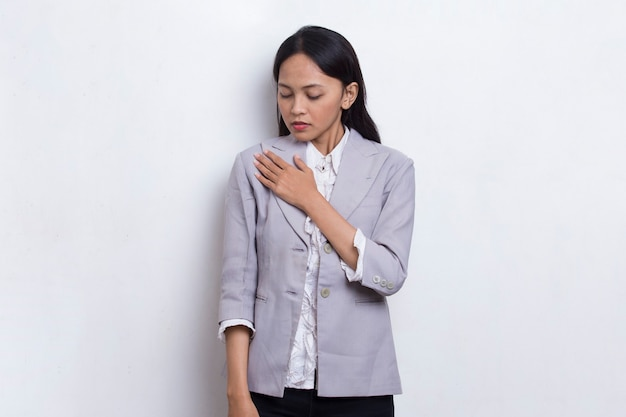Jonge mooie aziatische moslimvrouw die een hartaanval heeft die op witte achtergrond wordt geïsoleerd