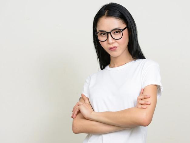 Jonge mooie aziatische nerdvrouw die geïsoleerde oogglazen draagt