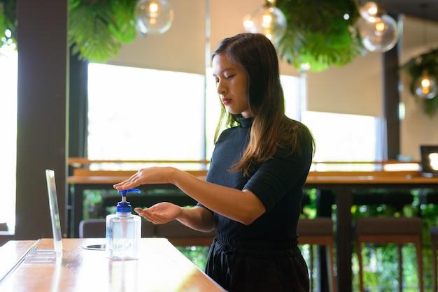 Jonge mooie aziatische onderneemster die handdesinfecterend middel als juiste hygiënetiquette gebruikt bij de koffiewinkel