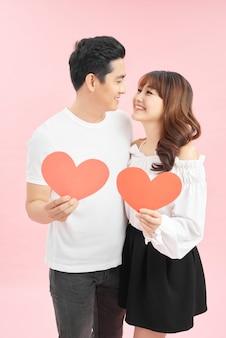 Jonge mooie aziatische paar met heden geïsoleerd op roze