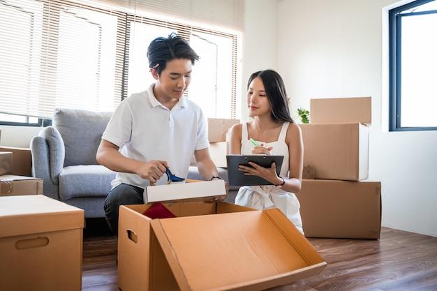 Jonge mooie aziatische paar verliefd verhuizen naar nieuw huis, zittend op de vloer erg blij en vrolijk voor nieuwe appartement rond kartonnen dozen en kartonnen dozen houden tijdens het verhuizen