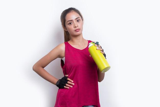 Jonge mooie aziatische sport vrouw drinkwater na training op witte achtergrond
