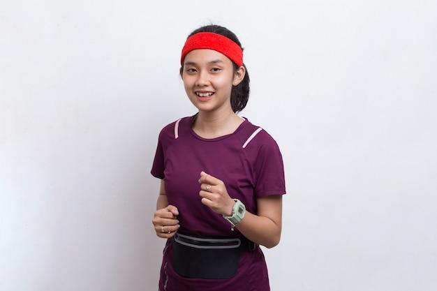 Jonge mooie aziatische sportieve vrouw die op witte achtergrond loopt
