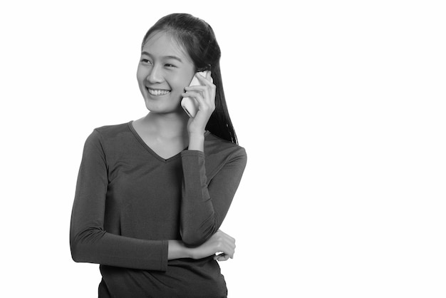 Jonge mooie aziatische tienermeisje geïsoleerd tegen een witte muur in zwart en wit