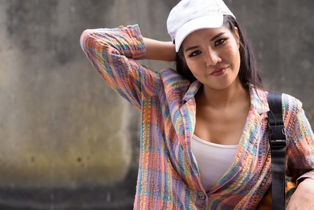 Jonge mooie aziatische toeristenvrouw die de stad onderzoekt