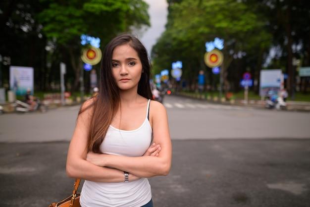 Jonge mooie aziatische toeristenvrouw die ho chi minh-stad i verkennen