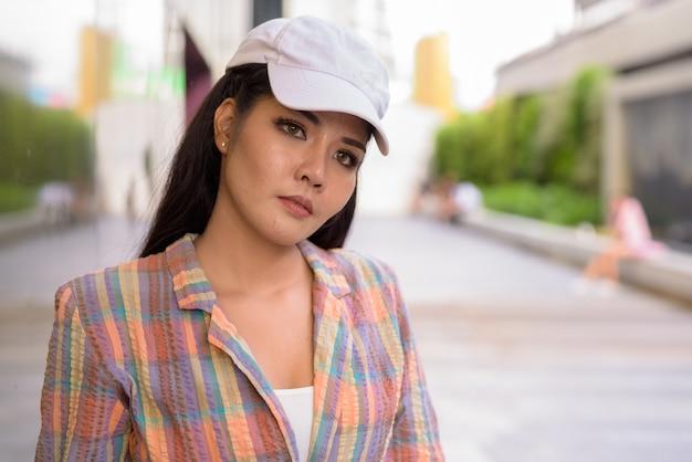 Jonge mooie aziatische toeristenvrouw die in openlucht denkt