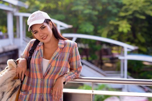 Jonge mooie aziatische toeristenvrouw die in openlucht glimlacht