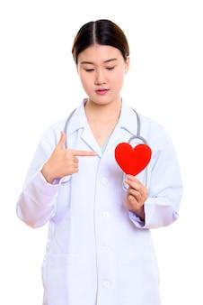 Jonge mooie aziatische vrouw arts die en op rood hart houdt
