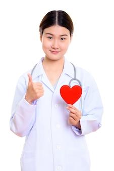 Jonge mooie aziatische vrouw arts die rood hart houdt en duim opgeeft