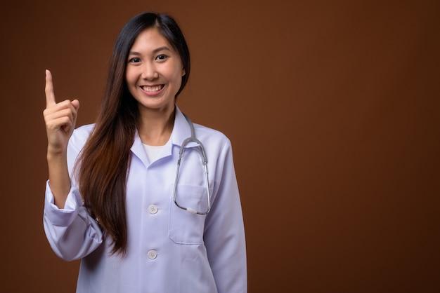 Jonge mooie aziatische vrouw arts tegen bruine achtergrond