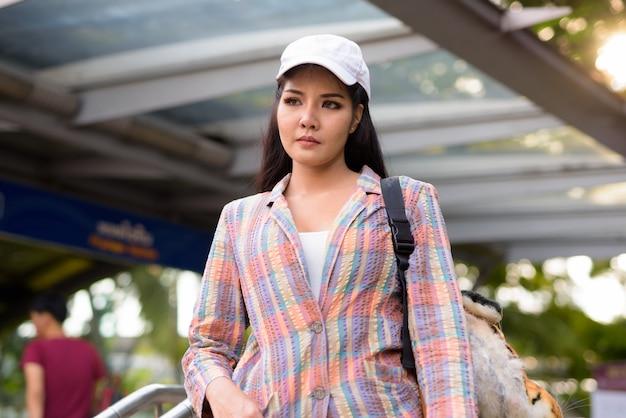 Jonge mooie aziatische vrouw buiten metrostation