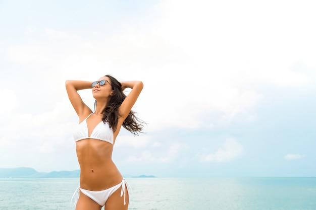 Jonge mooie aziatische vrouw die biniki het stellen draagt bij het strand in de zomer