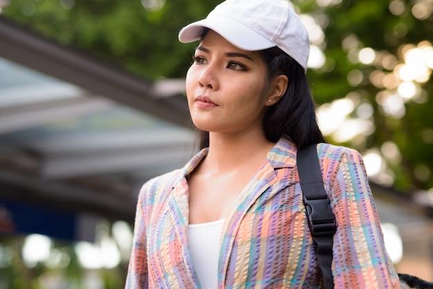 Jonge mooie aziatische vrouw die buiten metrostation denkt