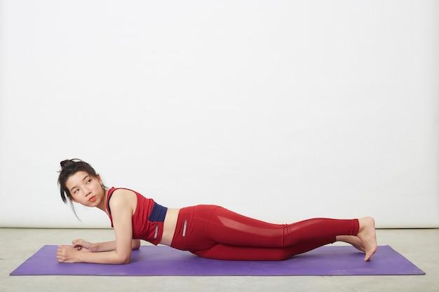 Jonge mooie aziatische vrouw die cobra poseert op een yogamat thuis, concept van gezond leven en natuurlijk evenwicht tussen lichaam en mentale ontwikkeling