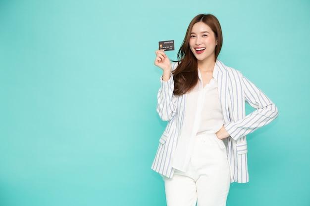 Jonge mooie aziatische vrouw die creditcard toont