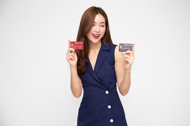 Jonge mooie aziatische vrouw die, die, creditcard glimlacht toont voor het doen van betaling of het betalen van online zaken