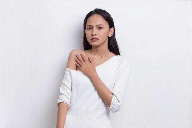 Jonge mooie aziatische vrouw die een hartaanval heeft die op witte achtergrond wordt geïsoleerd