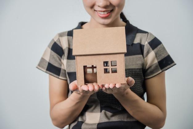 Jonge mooie aziatische vrouw die een huis in haar handen houdt, zwarte haren.