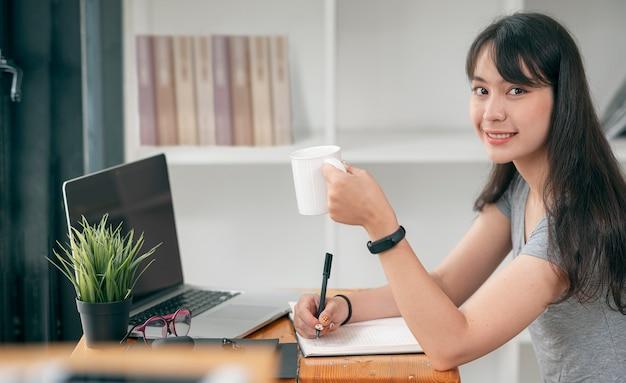 Jonge mooie aziatische vrouw die een mok vasthoudt, glimlacht en naar de camera kijkt terwijl ze thuis in de woonkamer werkt.