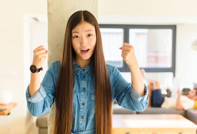 Jonge mooie aziatische vrouw die een ongelooflijk succes viert als een winnaar, die opgewonden en blij kijkt en zegt: