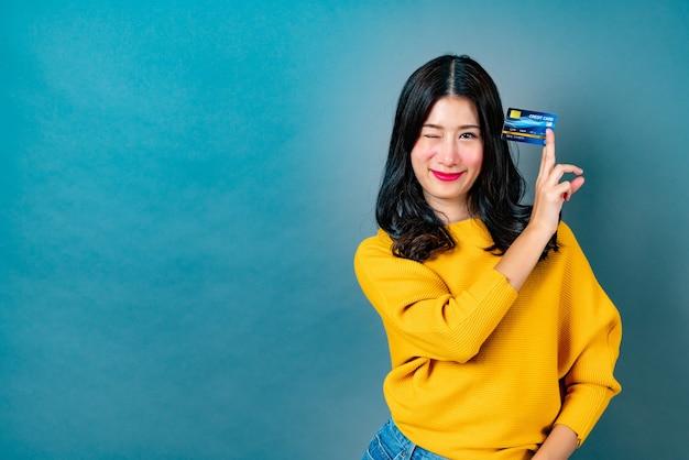 Jonge mooie aziatische vrouw die en creditcard in hand glimlacht voorstelt